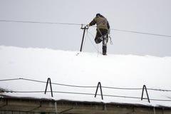 O trabalhador do serviço municipal cancela o telhado da neve acumulada no Imagens de Stock