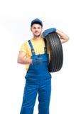 O trabalhador do serviço no uniforme azul mantém o pneu disponivel Imagem de Stock Royalty Free