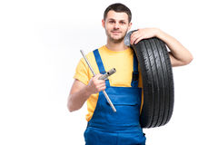 O trabalhador do serviço no uniforme azul mantém o pneu disponivel Fotos de Stock Royalty Free