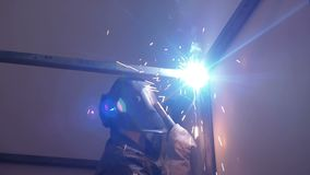 O trabalhador do soldador executa a soldadura do salto O soldador do trabalhador executa o processo da arco-soldadura de estrutur vídeos de arquivo