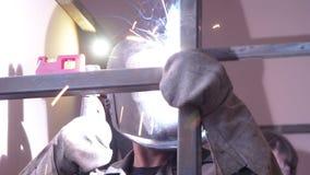 O trabalhador do soldador executa a soldadura do salto O soldador do trabalhador executa o processo da arco-soldadura de estrutur video estoque