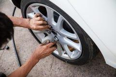 O trabalhador do técnico está parafusando o parafuso da roda com uma chave manual manutenção e de carro da inspeção conceito veri foto de stock