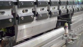 O trabalhador dobra a placa de metal na máquina industrial filme
