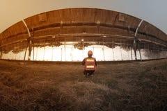 O trabalhador em calhas parabólicas solares das verificações do uniforme e do capacete imagens de stock