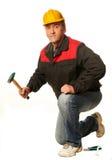 O trabalhador em um capacete de segurança amarelo agachou-se com um martelo, chave, plie Fotos de Stock