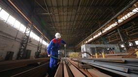 O trabalhador em um capacete do branco morde o fio de aço com cortadores de fio