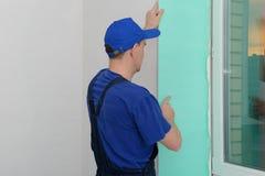 O trabalhador em um uniforme azul instala um painel do PVC foto de stock royalty free
