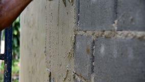 O trabalhador emplastra a parede do cimento filme