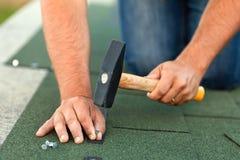 O trabalhador entrega a instalação de telhas do telhado do betume - colheita horizontal imagens de stock royalty free