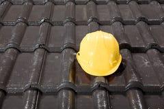 Capacete de segurança amarelo em telhas de telhado Fotos de Stock