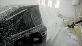 O trabalhador está cobrindo o corpo de carro pela espuma do sabão para lavar em uma garagem, usando a mangueira para pulverizar,  filme