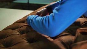 O trabalhador está cobrindo uma carcaça do sofá a tela, pelo esticão e pelo aperto