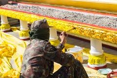 O trabalhador está pintando a cor do ouro no potenciômetro da vara de Joss Imagens de Stock Royalty Free
