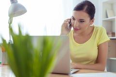 O trabalhador fêmea atrativo está usando a tecnologia moderna Foto de Stock Royalty Free