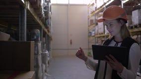O trabalhador fêmea do armazém faz o inventário e conta caixas com tabuleta digital à disposição filme