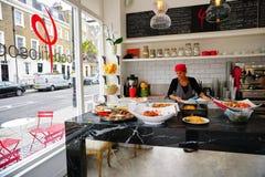 O trabalhador fêmea do restaurante prepara pratos saudáveis na cozinha do Street View fotos de stock royalty free