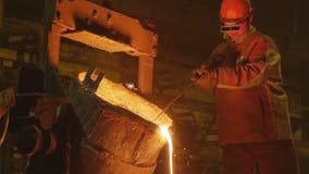 O trabalhador gerencie a cubeta e o metal derrama contra a escuridão video estoque