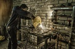 O trabalhador guarda as mãos a tubulação do metall para cortá-la na máquina Na perspectiva dos tijolos brancos Fotografia de Stock Royalty Free