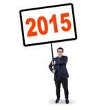 O trabalhador guarda uma placa com número 2015 Foto de Stock