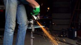 o trabalhador Homem-médio-envelhecido com a máquina de moedura angular está cortando o metal vídeos de arquivo