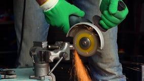 o trabalhador Homem-médio-envelhecido com a máquina de moedura angular está cortando o metal video estoque