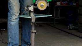 o trabalhador Homem-médio-envelhecido com a máquina de moedura angular está cortando o metal filme