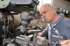 O trabalhador idoso olha o processamento do detalhe na máquina de trituração fotos de stock royalty free
