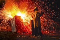 O trabalhador industrial que causa o chuveiro das faíscas para trás vê fotos de stock