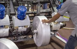 O trabalhador instala o rolo de filme para a máquina da extrusora do saco de plástico imagem de stock royalty free