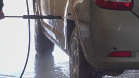 O trabalhador lava com cuidado o carro no fim da lavagem de carros acima vídeos de arquivo