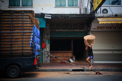 O trabalhador leva a cesta pelo ombro Imagens de Stock