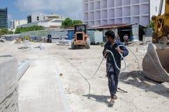 O trabalhador leva a mangueira Foto de Stock Royalty Free