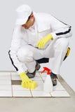 O trabalhador limpa com as telhas velhas da esponja e do pulverizador Imagem de Stock Royalty Free