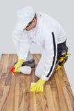 O trabalhador limpa com o assoalho de madeira da esponja e do pulverizador antes de lavrar Imagens de Stock Royalty Free