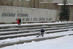 O trabalhador limpa a neve dos passeios com o snowblower no Mamaev Kurgan em Volgograd fotos de stock