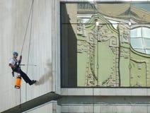 O trabalhador limpa a parede da construção Fotografia de Stock Royalty Free