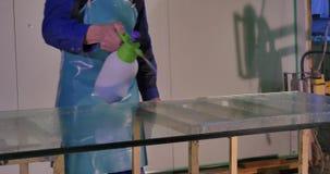 O trabalhador limpo e seca o vidro na fabricação A limpeza adulta meados de sorriso do trabalhador ensaboa o Sul na janela de vid video estoque