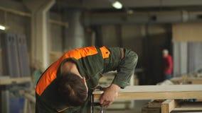 O trabalhador mói a madeira da máquina de moedura angular filme