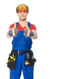 O trabalhador manual com as ferramentas que mostram os polegares levanta o sinal Imagem de Stock Royalty Free