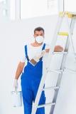 O trabalhador manual com pincel e pode inclinando-se na escada em casa Fotografia de Stock Royalty Free