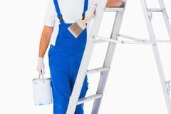 O trabalhador manual com pincel e pode na escada Fotografia de Stock Royalty Free