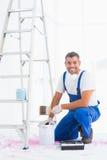 O trabalhador manual de sorriso com pincel e pode em casa Fotos de Stock