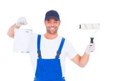 O trabalhador manual de sorriso com pintura pode e rolo Foto de Stock Royalty Free