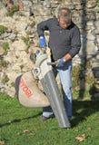 O trabalhador manual exterior limpa as folhas caídas Foto de Stock Royalty Free