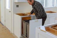O trabalhador manual instalou o escaninho de lixo das gavetas na cozinha foto de stock