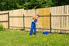 O trabalhador manual masculino que veste macacões azuis pinta a cerca de madeira Imagem de Stock