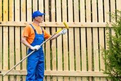 O trabalhador manual no uniforme de trabalho azul verifica a condição do rolo de pintura Fotografia de Stock Royalty Free