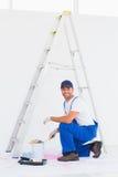 O trabalhador manual nos macacões que abrem a pintura pode em casa Foto de Stock Royalty Free