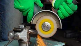 O trabalhador masculino com a máquina de moedura angular está cortando o metal video estoque