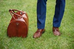 O trabalhador masculino está a mala de viagem próxima no gramado Imagem de Stock Royalty Free